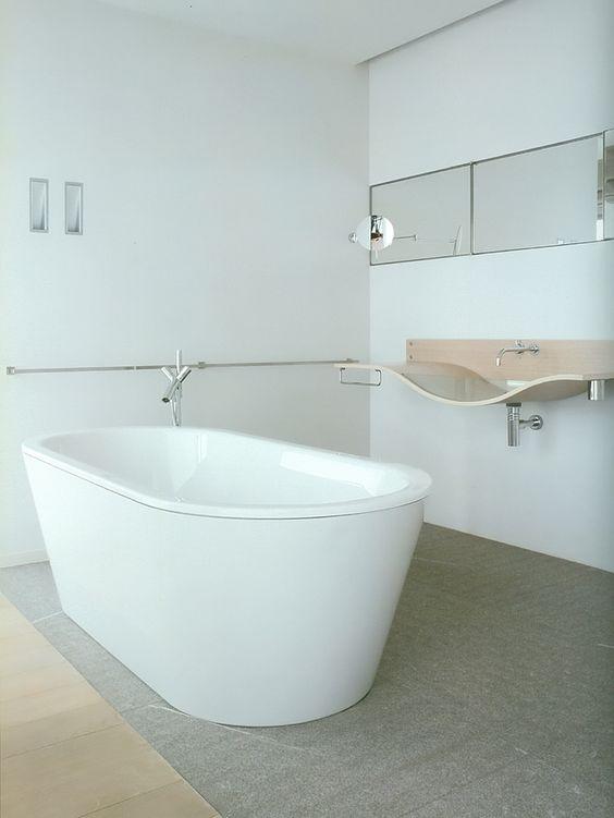 nowoczesne baterie łazienkowe, stojąca przy modernistycznej wannie i podtynkowa nad oryginalną umywalką