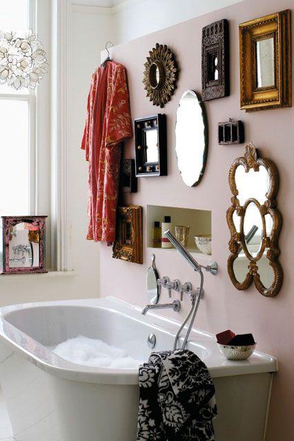 baterie łazienkowe zamontowane pod tynkiem do wanny przyściennej. na ścianie wypełnionej lustrami w różnych wielkościach i kształtach