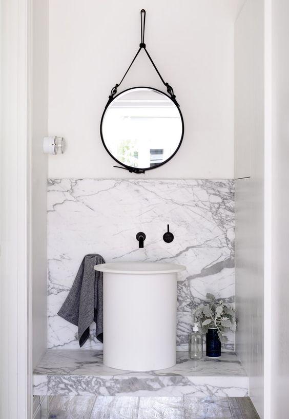 marmurowa łazienka z umywalką w kształcie wiadra z czarna podtynkową baterią