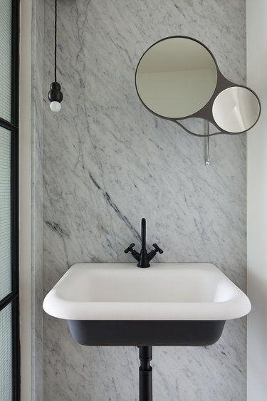 marmurowa łazienka wykończona czarnymi dodatkami w tym umywalką, baterii umywalkowej i oświetlenia sufitowego