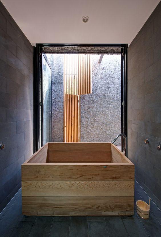 baterie łazienkowe w nietypowej łazience z dużą drewniana wanną, wylewką wannową stojąca obok niej i z mieszaczem w ścianie