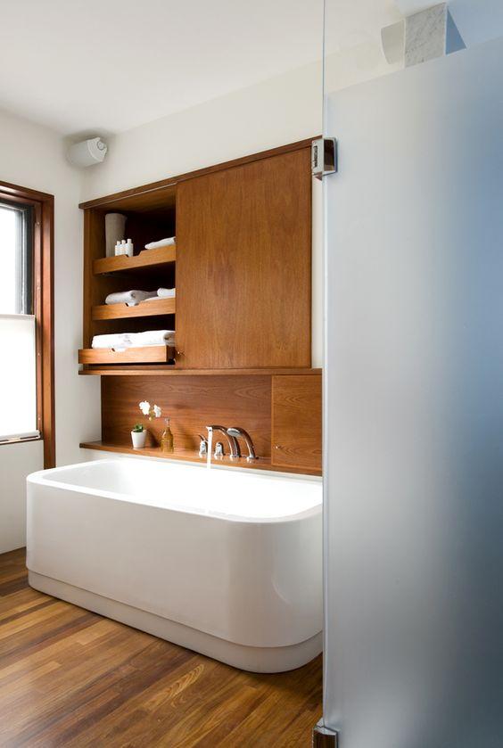 baterie łazienkowe zamontowane na drewnianej półce obok wanny