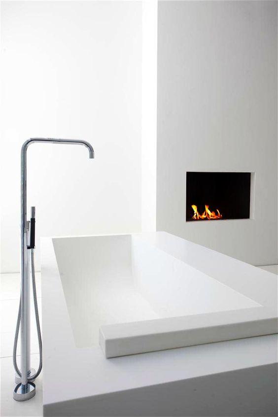 baterie łazienkowe, stylizowana stojąca wylewka z nowoczesną wanną w łazience z kominkiem