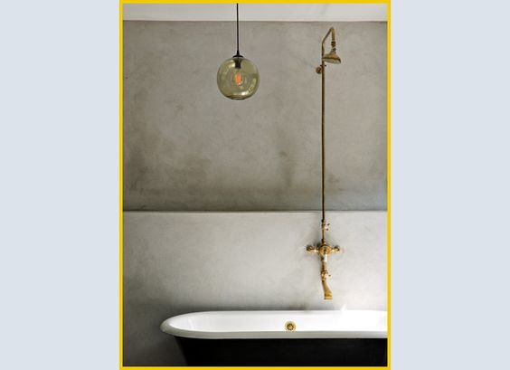 złote baterie łazienkowe ścienne w surowej łazience z nowoczesnym oświetleniem