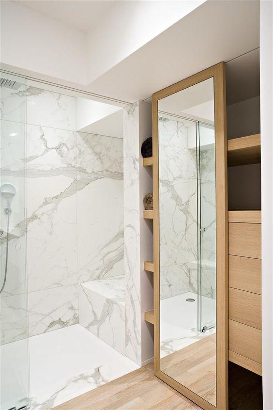 marmurowa łazienka w połączeniu z drewnianymi pułkami i szufladami daje efekt elegancji