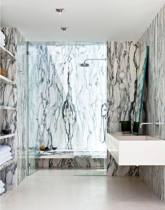 Mocno wzorzysta marmurowa łazienka z marmurowymi półkami i wykończeniem prysznica