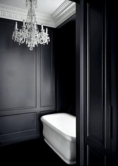 stylizowana czarna łazienka  z czarną boazerią na ścianach z białą wanną i kryształowym żyrandolem