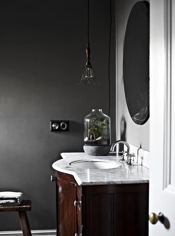 czarne ściany w stylizowanej łazience, umywalka przykryta jasnym marmurem