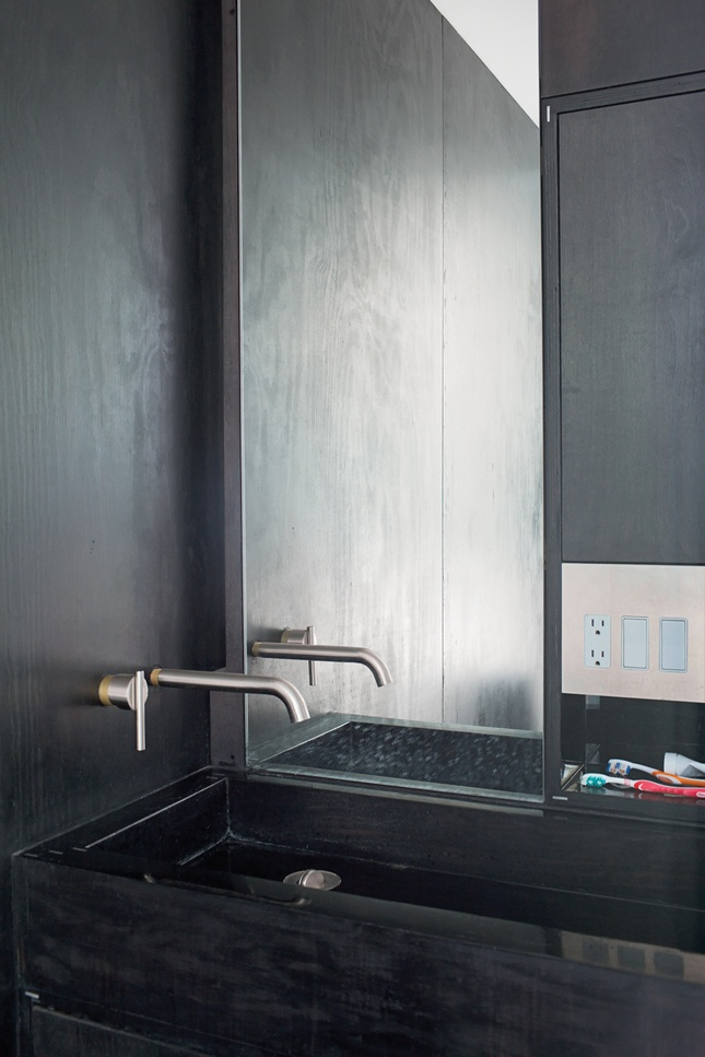 czarne drewno w łazience połączone z kamienną również czarną umywalką z kamienia