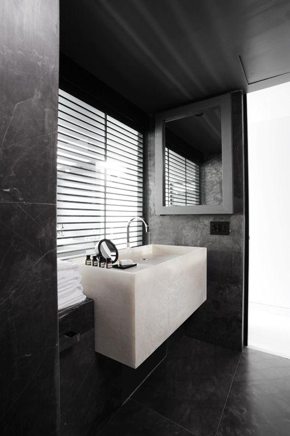 Czarna łazienka przełamana białą kamienną umywalką
