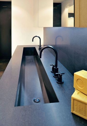 czarny konglomerat na ścianie łazienki oraz jako materiał z którego zrobiona została podłużna umywalka