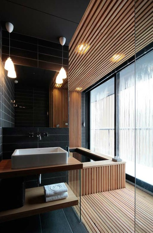 jasne drewno w czarnej łazience wydziela część kąpielową