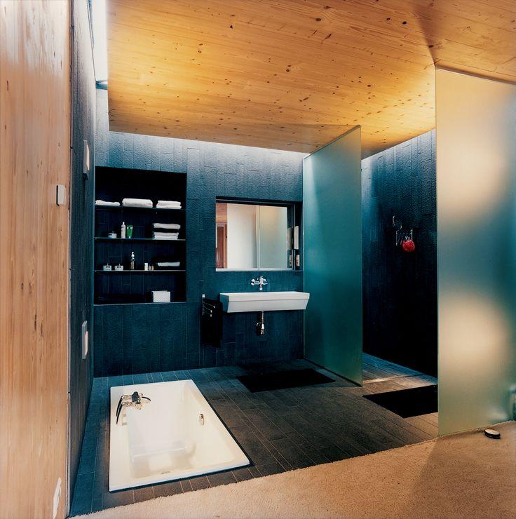 Czarna łazienka ocieplona wizualnie przez sosnowe deski położone na ścianie i suficie