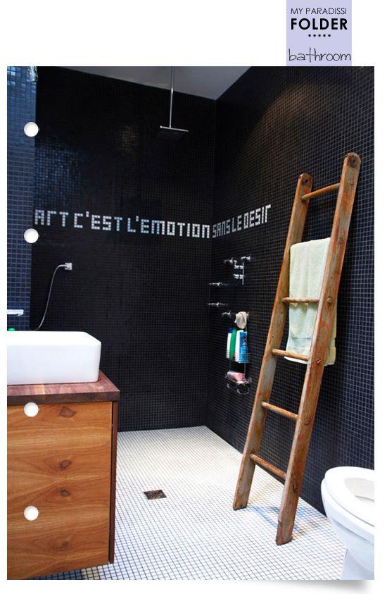 czarna łazienka w połaczeniu z drewnianymi dodatkami w postaci drabinki i szafeczki ocieplają jej wizerunek