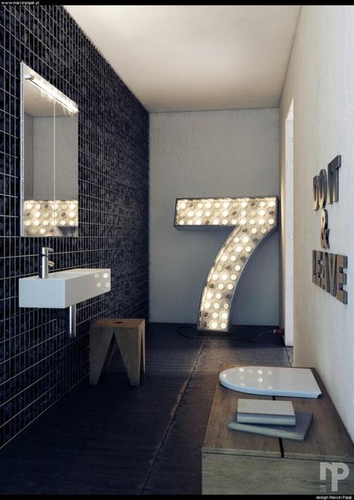 minimalistyczna czarna łazienka z dodatkiem w postaci dużej świecącej siódemki daje nietuzinkowe połączenie