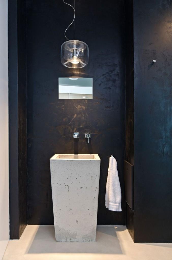 czarna łazienka wyposażona w wysoką surową betonową umywalkę w kształcie kwadratowej donicy i nowoczesną lampę
