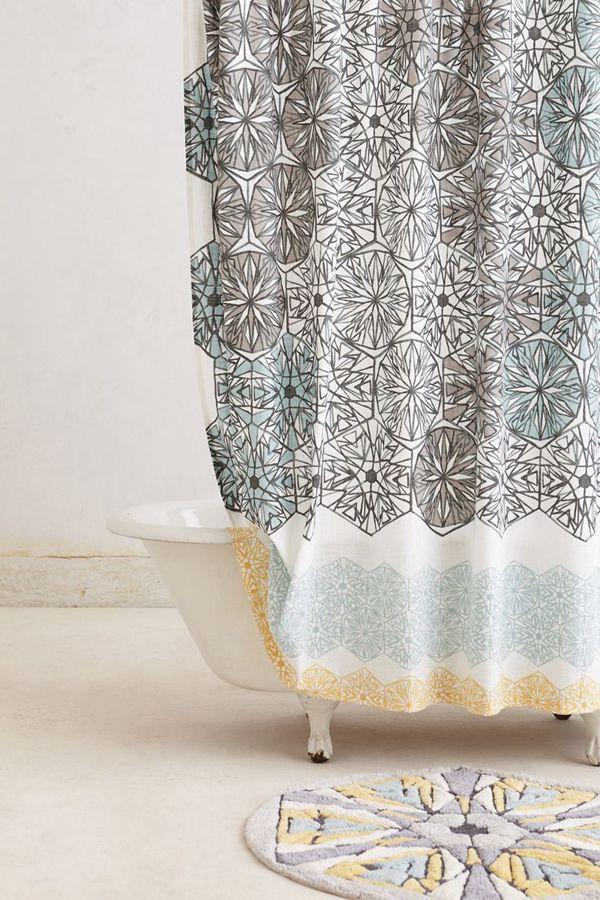 wzorzysta zasłona prysznicowa użyta do zasłonięcia wanny i dywanik dopasowane kolorystycznie
