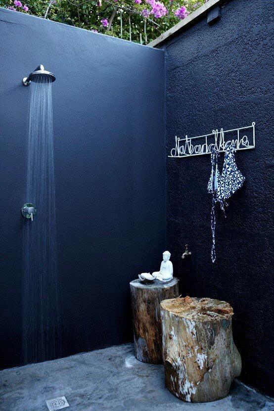 aranżacja łazienki na zewnątrz z ciemnymi ścianami i betonową podłogą bez dachu