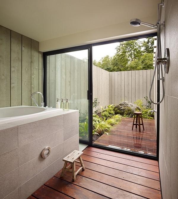 aranżacja łazienki z dużym oknem przesuwnym, które łączy ją z tarasem gdzie zastosowali identyczną podłogę