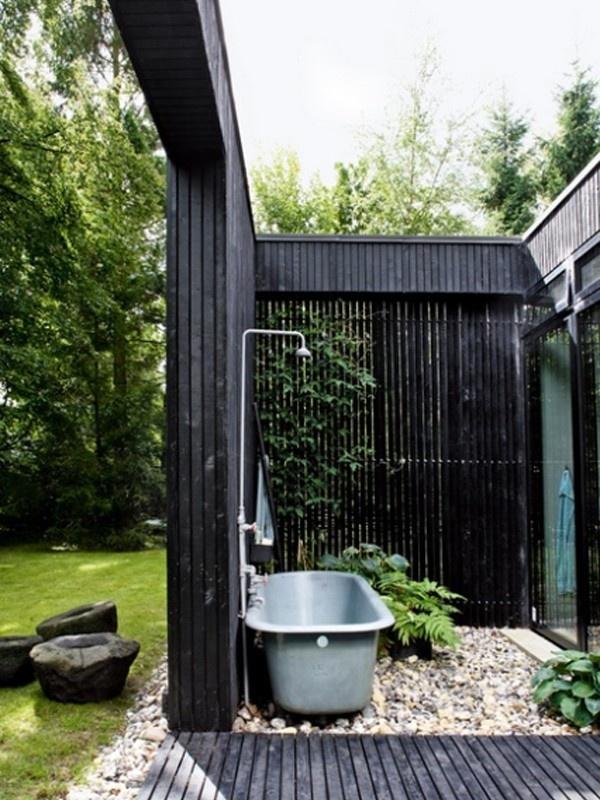 aranżacja łazienki w ogrodzie, stalowa wanna na otoczakach w otoczeniu zieleni