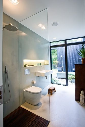 stojąca miska ustępowa stojąca koło kabiny walk in w łazience z wielkim oknem z wyjściem na ogród