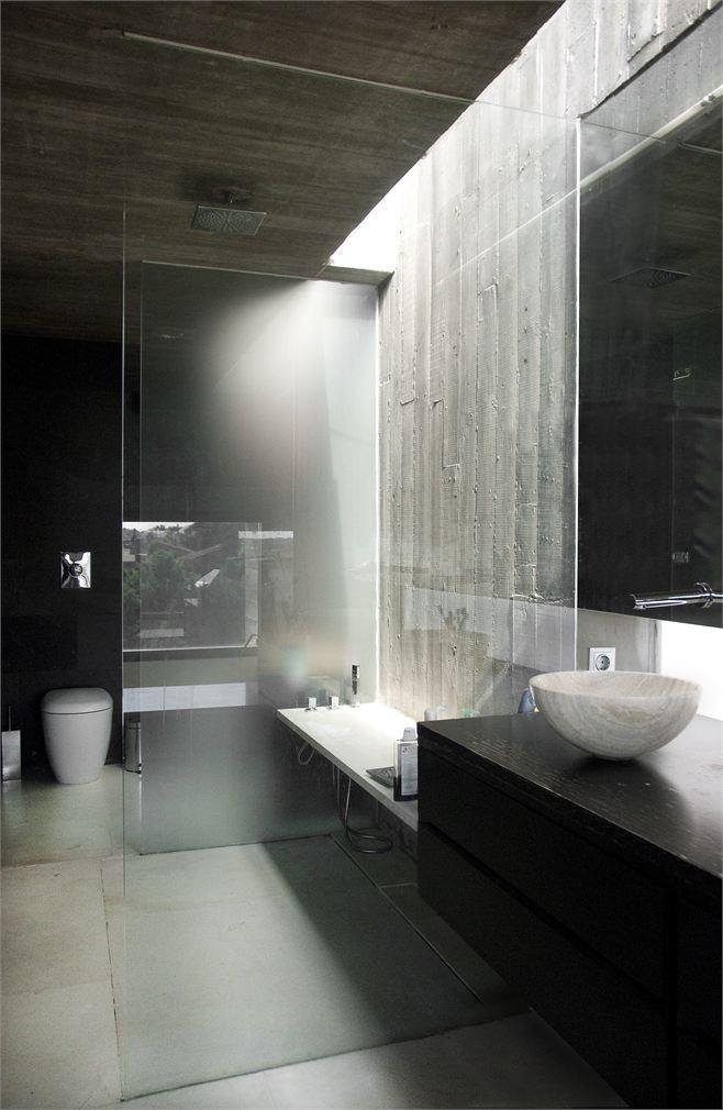 jasna umywalka z kamienia w półsferycznym kształcie w nowoczesnej ciemnej łazience