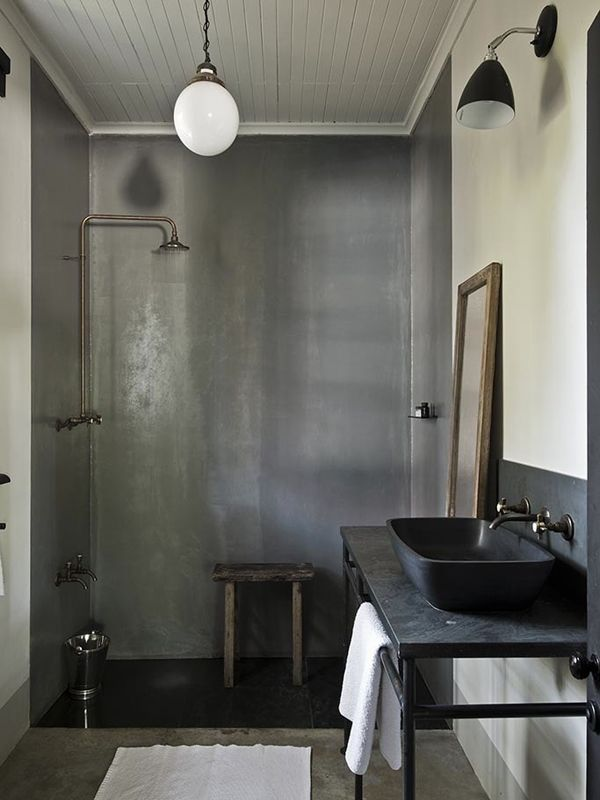 podłużna umywalka z z kamienia w kolorze czarnym w połączeniu z czarnym blatem i srebrnym wykończeniem części prysznica