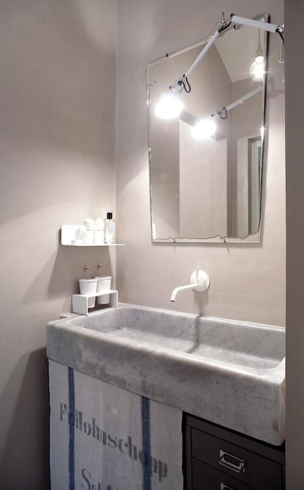podłużna umywalka z kamienia w połączeniu z nowoczesną, białą baterią podtynkową