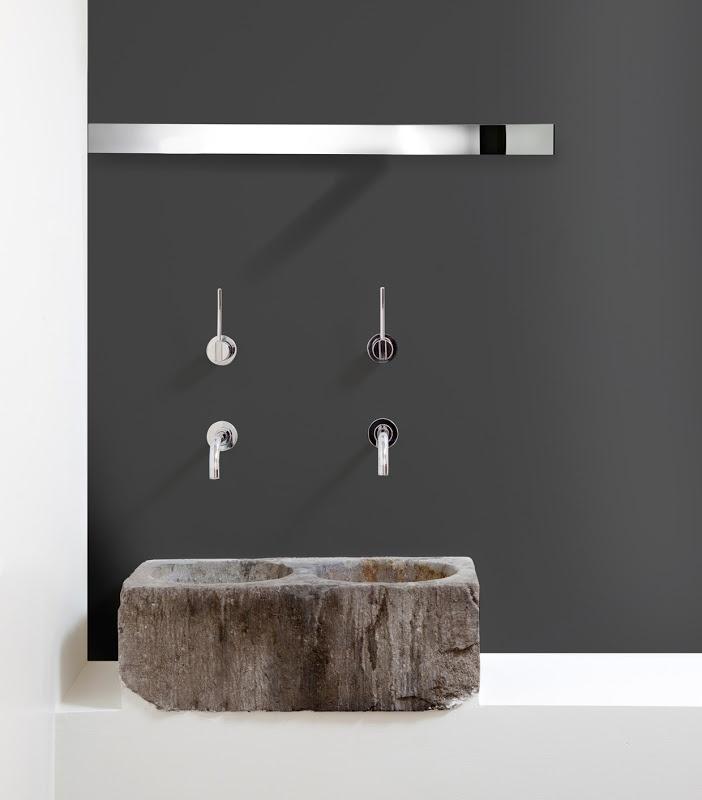 podwójna umywalka z kamienia - monioit wykończona podtynkowymi bateriami i na szarym tle ściany