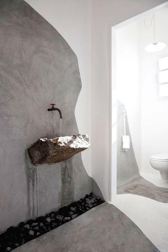 oryginalna umywalka z kamienia o wyglądzie nie obrobionego kamienia, woda zapewne celowo spływa po ścianie a odpływ jest pod otoczakami na podłodze