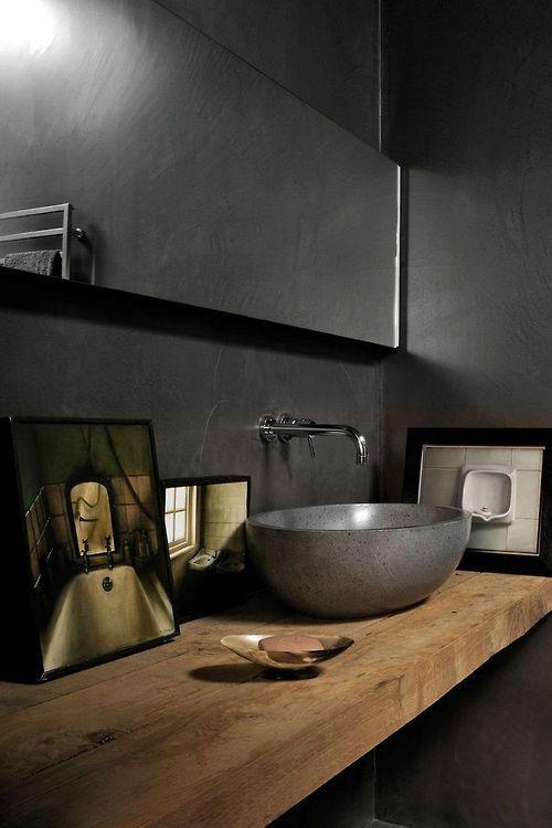 półsferyczna umywalka z kamienia w ciemnej łazience z podtynkową baterią