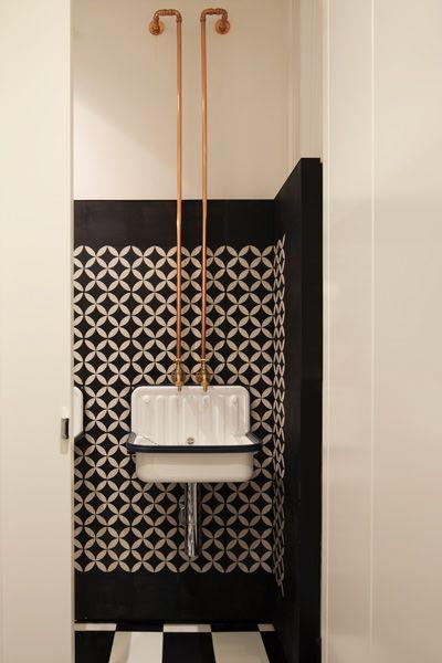 Miedziane rurki do wody poprowadzone po ścianie, industrialna umywalka w łazience w bibliotece w tylu skandynawskim