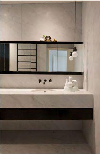 biały marmur w kontraście z czarnymi wykończeniami i dodatkami nadaje łazience prosty skandynawski styl
