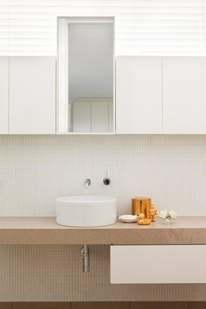 jasna łazienka w stylu skandynawskim w małej mozaice o nietypowym kształcie, z dodatkiem beżowego kamienia i złotych ozdobników