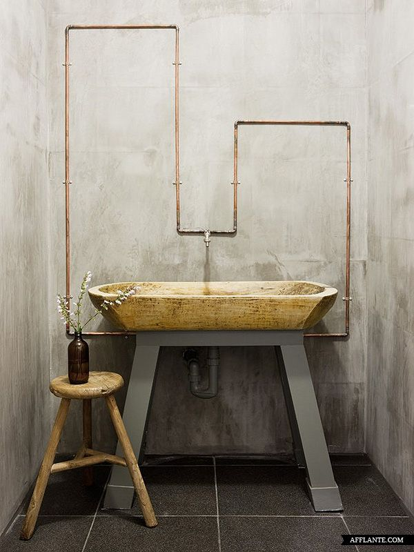 Nietypowa drewniana umywalka w zestawieniu z szarymi ścianami z betonu, miedziane rurki poprowadzone po ścianie, nie ma lustra co również jest odmianą! Łazienka skandynawska