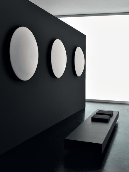 białe, okrągłe, ścienne grzejniki łazienkowe na czarnym tle ściany