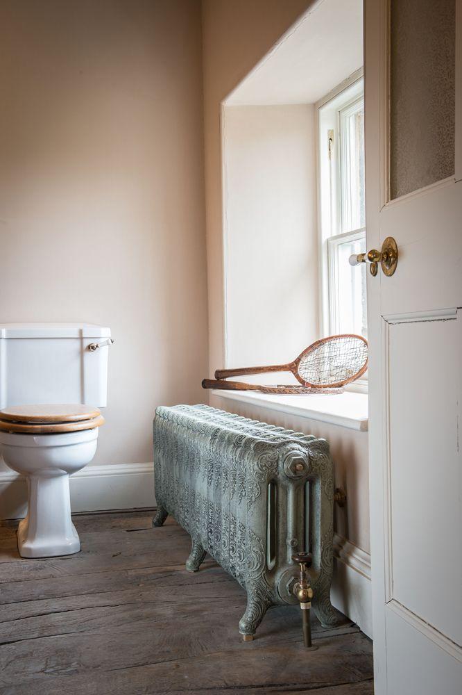 stylizowane grzejniki łazienkowe na nóżkach w toalecie pod oknem