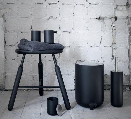 czarne akcesoria łazienkowe: kos, szczotka do wc, pojemniki na drobiazgi i taboret