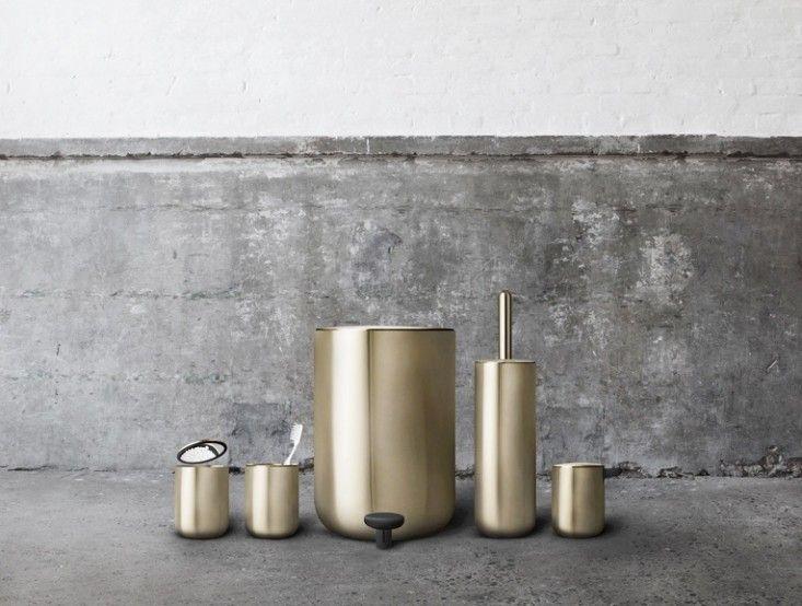 złote akcesoria łazienkowe na tle betonowej ściany
