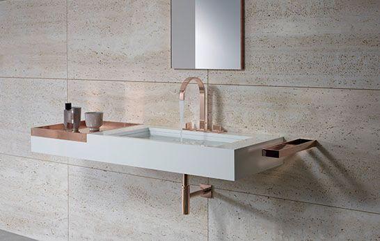syfon, bateria umywalkowaoraz akcesoria w kolorze różowego złota zdobią łazienkę w trawertynie