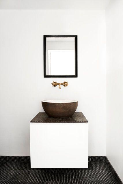 ścienna bateria umywalkowa w kolorze mosiądzu w otoczeniu kamiennej umywalki i lustra w ciemnej ramie