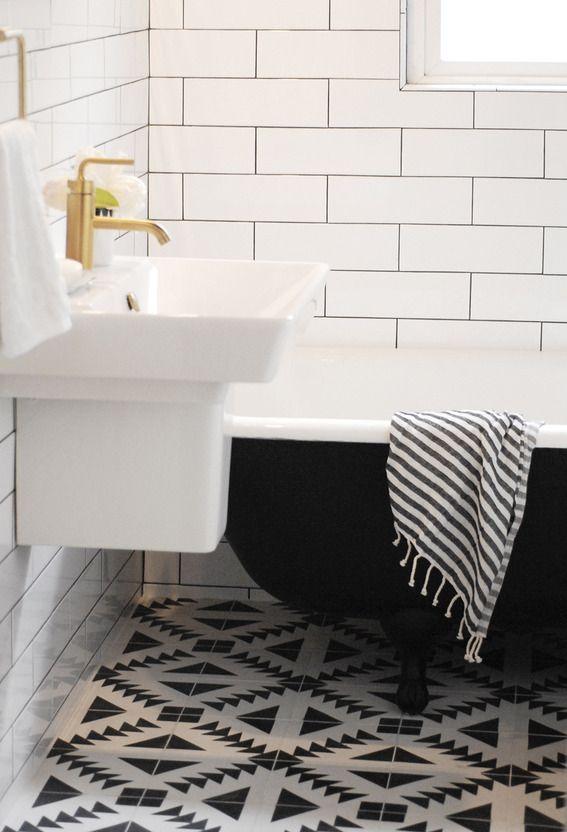 złota bateria umywalkowa w zestawieniu z białymi ścianami i wzorzystą podłogą w skandynawskim wydaniu