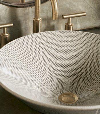 eramiczna wzorzysta umywalka w złote kropki, dopasowana do niej złota bateria.