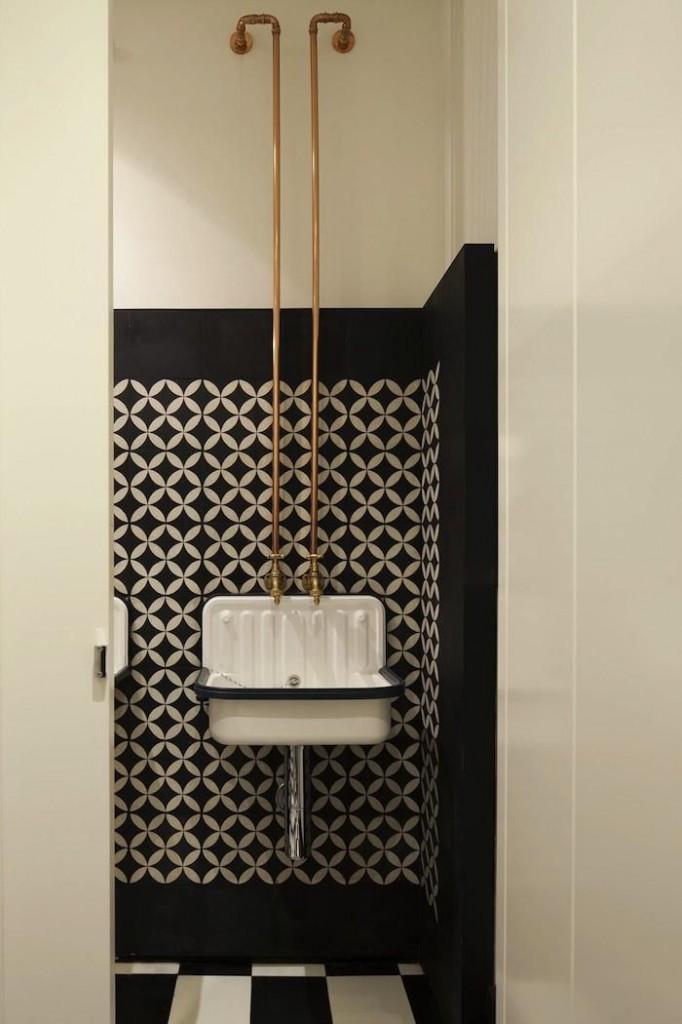 instalacja w łazience w formie miedzianych naściennych rur poprowadzonych z górnej części ściany