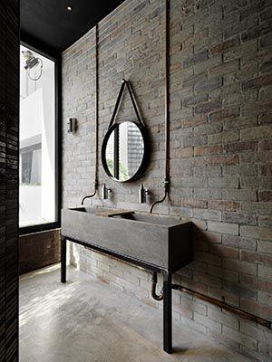 baterie umywalkowe w typowej łazience industrialnej, z ceglaną ścianą,betonową podłogą z instalacją naścienną