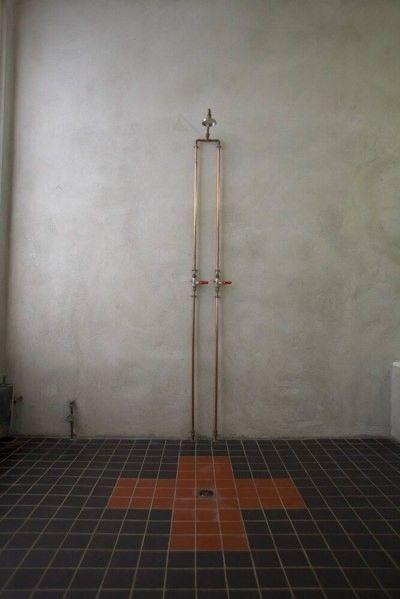 instalacja w łazience industrialnej, betonowe surowe ściany i czarno płytko podłogowe
