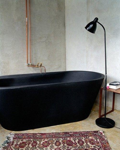 beton na ścianie, modernistyczna, czarna wanna i industrialna instalacja w łazience