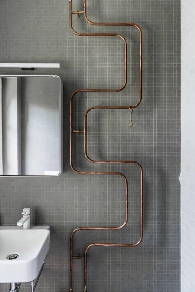 Instalacja w łazience w postaci miedzianych rurek i poprowadzone po ścianie
