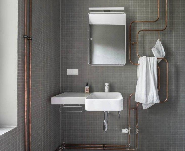 miedziana instalacja w łazience prowadzona po ścianie tworzy wieszak na ręczniki.