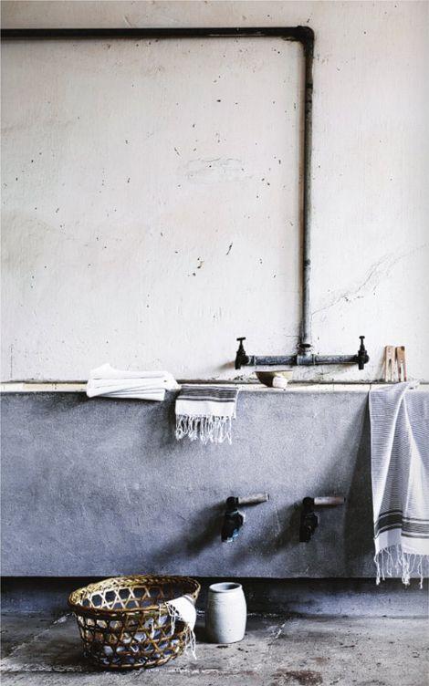 w betonowej łazience czarne rurki do wody prowadzone po ścianie
